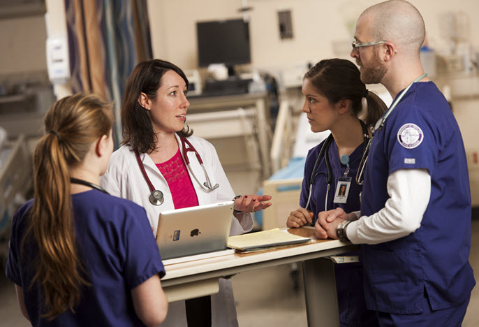 2 nursing students and a professor talking in Nursing Sim Lab
